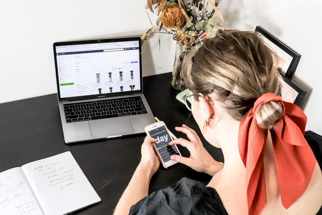 mulher ao telemóvel com um computador